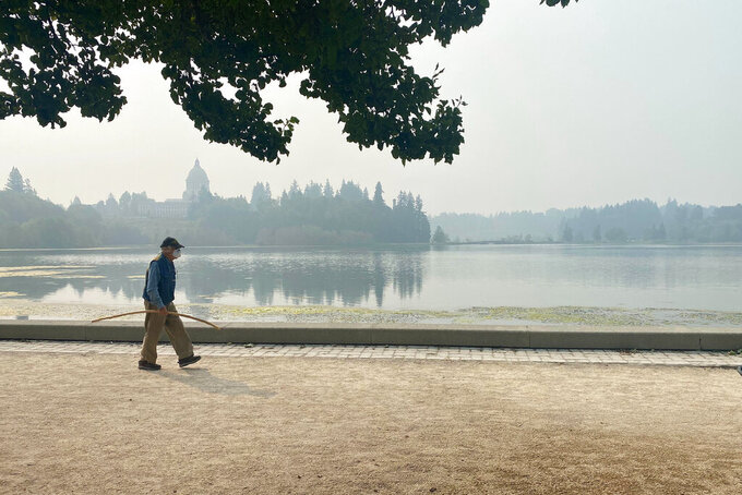 A man wearing a mask walks by the lake outside of the Washington State Capitol in Olympia, Wash., Friday, Sept. 11, 2020. Olympia is among the places facing unhealthy air quality due to wildfires in the Pacific Northwest. (AP Photo/Rachel La Corte)