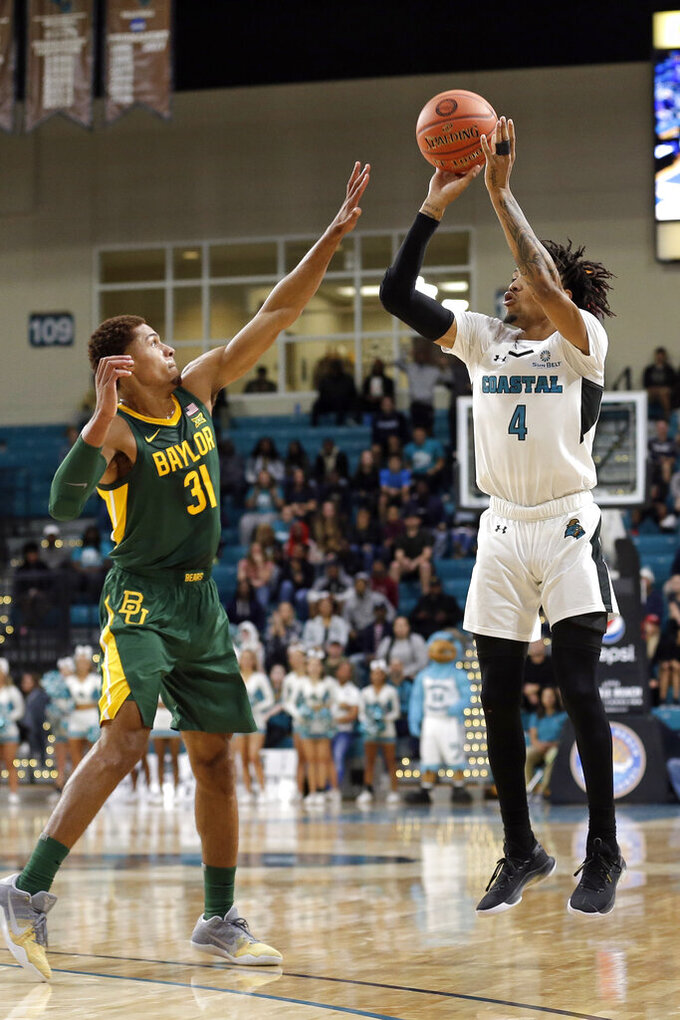 Coastal Carolina guard Keishawn Brewton (4) shoots while Baylor guard MaCio Teague (31) defends during the first half of an NCAA college basketball game at the Myrtle Beach Invitational in Conway, S.C., Friday, Nov. 22, 2019. (AP Photo/Gerry Broome)