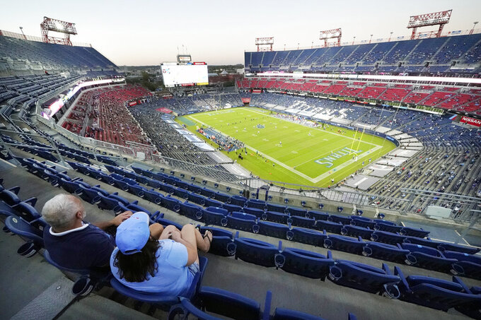 Greg McKinney, left, and Dawna Ebberts, of Vancouver, Wash., watch the Tennessee Titans and the Buffalo Bills play in the first half of an NFL football game Tuesday, Oct. 13, 2020, in Nashville, Tenn. The game is the first Titans home game this season where a restricted number of fans are allowed in the stadium. (AP Photo/Mark Humphrey)
