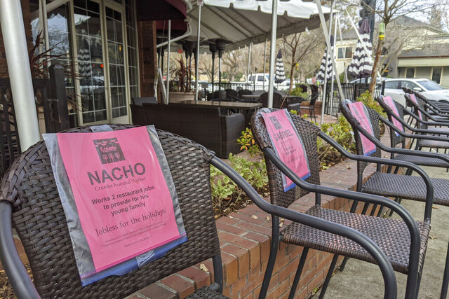 This Monday, Dec. 21, 2020, photo shows a line of empty chairs bearing the names of workers who have lost their jobs during the pandemic, outside Crumbs restaurant in Danville, Calif. (AP Photo/Michael Liedtke)