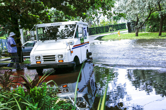 FILE - In this June 19, 2019 file photo, a postal worker returns to their truck parked on a flooded street in Miami caused by high tides. Flooding due to climate change-related sea level rising, the erosion of natural barriers and long-periods of rain pose substantial economic risks to Florida, particularly its real estate value, according to two new reports released last week. (AP Photo/Ellis Rua, File)