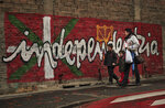 FILE - In this Jan. 12, 2011 file photo, people walk past a wall with painted words in Basque that reads: