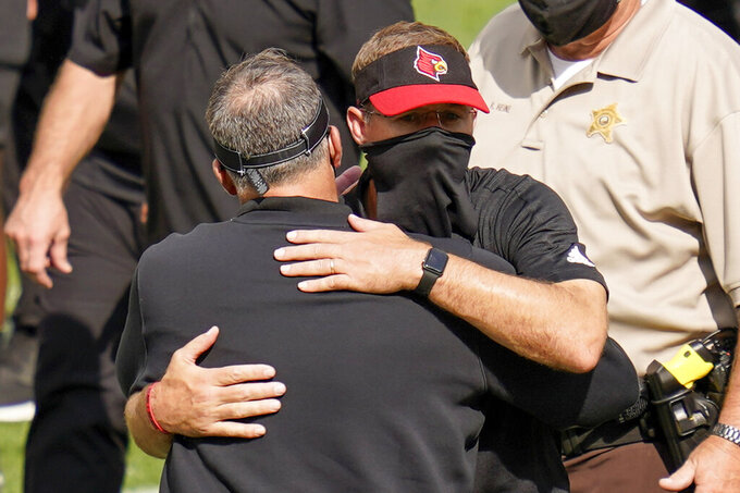 Louisville head coach Scott Satterfield, right, hugs Pittsburgh head coach Pat Narduzzi after an NCAA college football game, Saturday, Sept. 26, 2020, in Pittsburgh. Pittsburgh won 23-20.(AP Photo/Keith Srakocic)