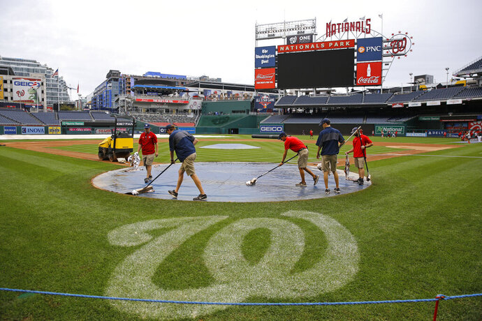 Groundskeepers remove rainwater from a tarp covering home plate during a baseball workout session, Monday, Sept. 30, 2019, in Washington. The Washington Nationals are scheduled to host the Milwaukee Brewers in a National League wild card game Tuesday, Oct. 1. (AP Photo/Patrick Semansky)