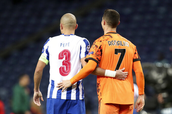 Porto's Pepe, left, and Juventus' Cristiano Ronaldo embrace at the end of the Champions League round of 16, first leg, soccer match between FC Porto and Juventus at the Dragao stadium in Porto, Portugal, Wednesday, Feb. 17, 2021. (AP Photo/Luis Vieira)