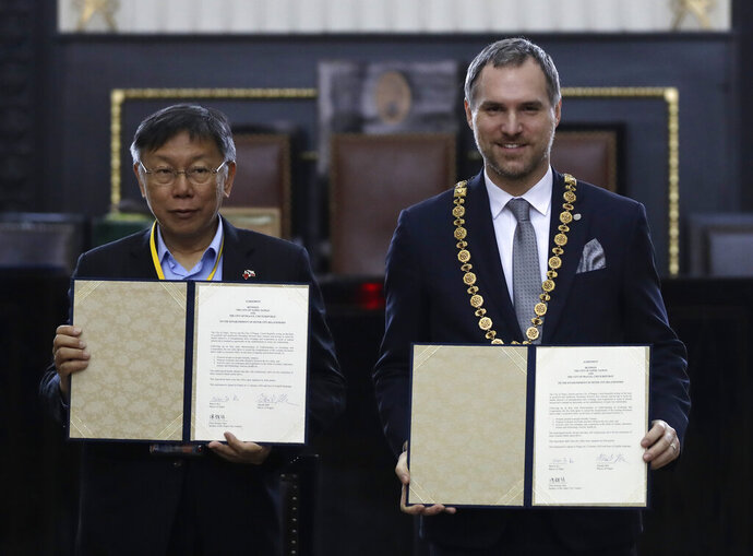Mayor of Prague Zdenek Hrib, right, and Taipei city mayor Ko Wen-je display a partnership agreement between the two cities at at the Old Town City Hall in Prague, Czech Republic, Monday, Jan. 13, 2020. The signing comes three months after Prague revoked a similar sister-city agreement with Beijing, an action that angered China. (AP Photo/Petr David Josek)