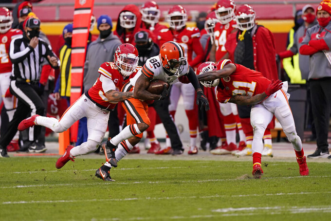 Cleveland Browns wide receiver Rashard Higgins (82) runs from Kansas City Chiefs safety Juan Thornhill, left, and cornerback Bashaud Breeland, right, after catching a pass during the second half of an NFL divisional round football game, Sunday, Jan. 17, 2021, in Kansas City. (AP Photo/Charlie Riedel)