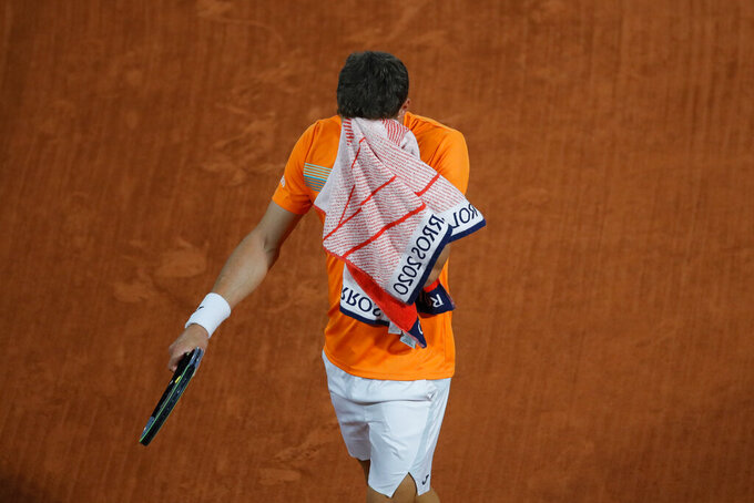 Spain's Pablo Carreno Busta wipes his face in the fourth round match of the French Open tennis tournament against Germany's Daniel Altmaier at the Roland Garros stadium in Paris, France, Monday, Oct. 5, 2020. (AP Photo/Christophe Ena)