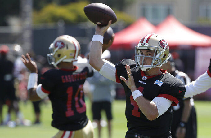 San Francisco 49ers quarterback Nick Mullens, right, throws a pass at the team's NFL football training camp in Santa Clara, Calif., Monday, July 29, 2019. (AP Photo/Jeff Chiu)