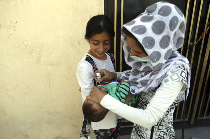 A health worker administers a vaccination to a child during a polio campaign in the old part of Kabul, Afghanistan, Tuesday, June 15, 2021. Gunmen on Tuesday targeted members of polio teams in eastern Afghanistan, killing some staffers, officials said. (AP Photo/Rahmat Gul)