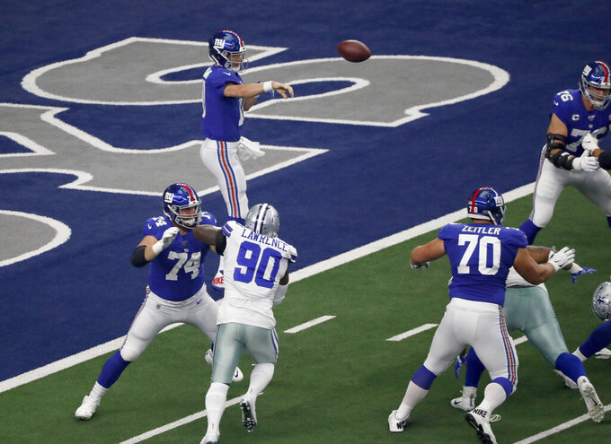 New York Giants quarterback Eli Manning (10) throws a pass as offensive guard Mike Remmers helps against pressure from Dallas Cowboys defensive end Demarcus Lawrence (90) in the first half of a NFL football game in Arlington, Texas, Sunday, Sept. 8, 2019. (AP Photo/Roger Steinman)