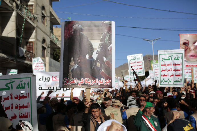 A Houthi supporter holds a poster with Arabic writing that reads
