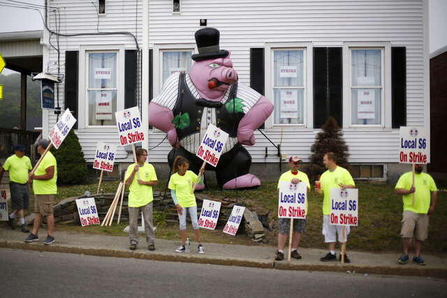 Strikers picket outside the district lodge of Local 6 across from Bath Iron Works, Monday, June 22, 2020, in Bath, Maine. Production workers at one of the Navy's largest shipbuilders overwhelmingly voted to strike, rejecting the company's three-year contract offer Sunday and threatening to further delay delivery of ships. (AP Photo/Robert F. Bukaty)