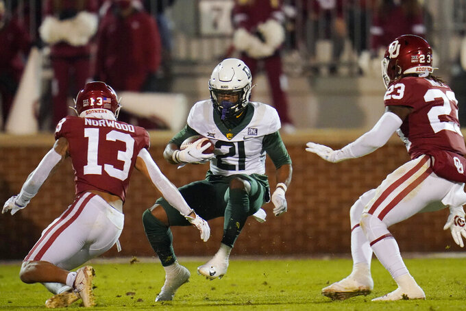 Baylor wide receiver Josh Fleeks (21) carries between Oklahoma defensive back Tre Norwood (13) and linebacker DaShaun White (23) during the first half of an NCAA college football game Saturday, Dec. 5, 2020, in Norman, Okla. (AP Photo/Sue Ogrocki)