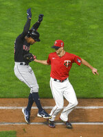 Minnesota Twins pitcher Taylor Rogers, right,tags out Cleveland Indians' Oscar Mercado after Mercado hit a short ground ball, for the final out of a baseball lgame Friday, Sept. 11, 2020, in Minneapolis. The Twins won 3-1. (AP Photo/Craig Lassig)