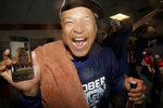 Los Angeles Dodgers manager Dave Roberts holds a cell phone during a video conference with injured infielder Max Muncy, during a lockerroom celebration after the Dodgers defeated the Baltimore Orioles 7-3 during a baseball game Tuesday, Sept. 10, 2019, in Baltimore. The Dodgers clinched the NL West title. (AP Photo/Julio Cortez)