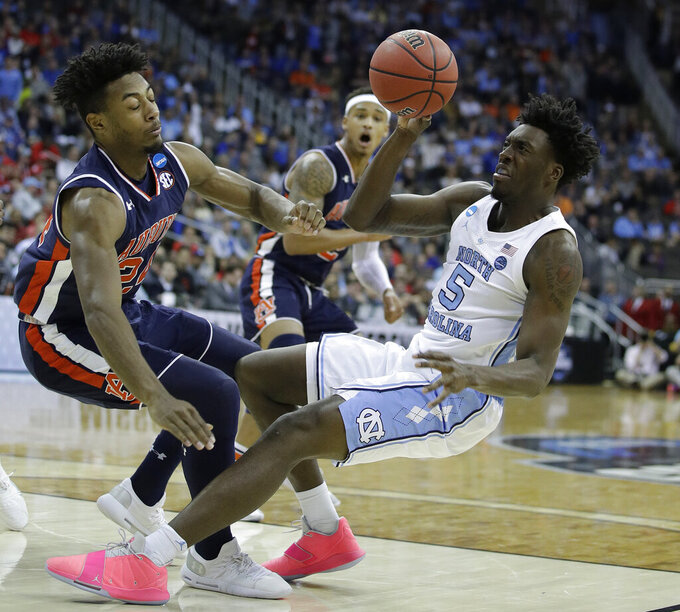 North Carolina's Nassir Little (5) tries to get off a shot as Auburn's Anfernee McLemore and Bryce Brown (2) defend during the first half of a men's NCAA tournament college basketball Midwest Regional semifinal game Friday, March 29, 2019, in Kansas City, Mo. (AP Photo/Charlie Riedel)
