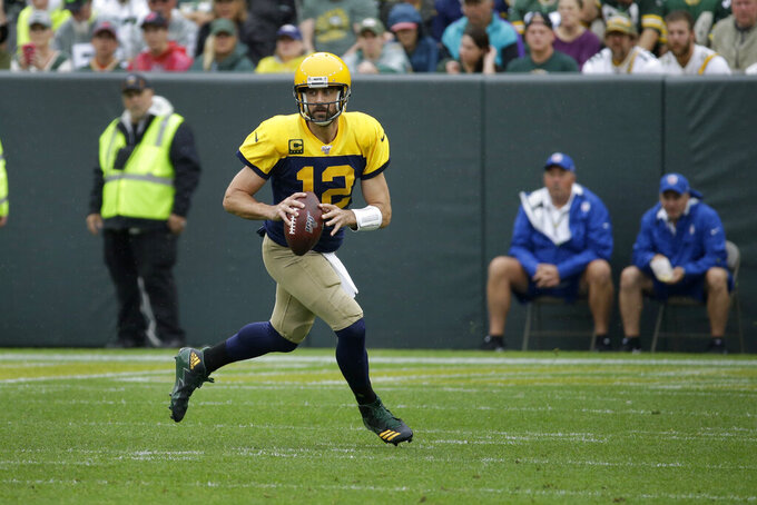 Green Bay Packers quarterback Aaron Rodgers rolls out to pass during the first half of an NFL football game against the Denver Broncos, Sunday, Sept. 22, 2019, in Green Bay, Wis. (AP Photo/Mike Roemer)