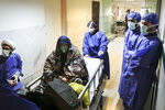 FILE - In this March 7, 2020 file photo, a patient infected with the new coronavirus is moved, at Baqiyatallah Al'Azam Hospital that is affiliated to the Revolutionary Guard, in Tehran, Iran. While crippling sanctions imposed by the U.S. government left the country ill-equipped to deal with the fast-moving virus, some medical professionals say government and religious leaders bear the brunt of the blame for allowing the virus to spread -- and for hiding how much it had spread. (Mohammad Hasan Zarifmanesh/Tasnim News Agency via AP, File)