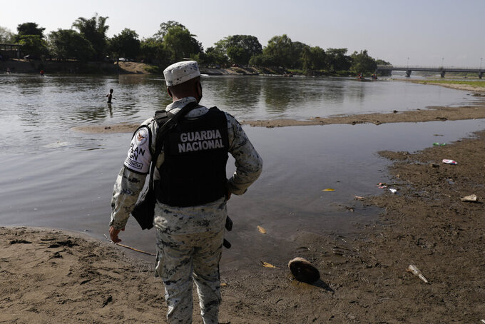 FILE - In this March 21, 2021 file photo, a Mexican National Guard stands on the bank of the Suchiate River, the natural border with Guatemala and Mexico, near Ciudad Hidalgo, Mexico, as part of an operation on Mexico's southern border to crack down on migrant smuggling. President Andrés Manuel López Obrador said on Tuesday, June 15, 2021, he plans to make the National Guard part of the army, after it was created as a civilian-controlled force two years prior. (AP Photo/Eduardo Verdugo, File)