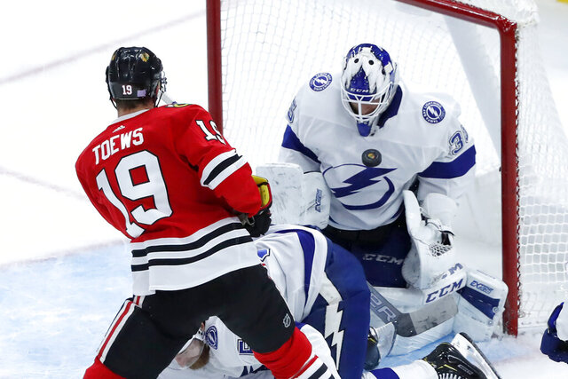 Tampa Bay Lightning goaltender Curtis McElhinney (35) makes a chest save on a shot by Chicago Blackhawks' Jonathan Toews during the second period of an NHL hockey game Thursday, Nov. 21, 2019, in Chicago. (AP Photo/Charles Rex Arbogast)