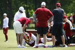 Washington Redskins president Bruce Allen rests his hand on linebacker Reuben Foster's helmet after Foster suffered an injury during a practice at the team's NFL football practice facility, Monday, May 20, 2019, in Ashburn, Va. (AP Photo/Patrick Semansky)