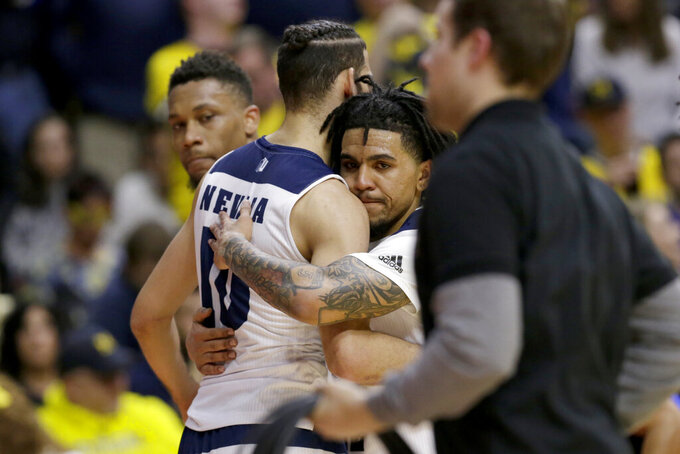 Nevada's Jazz Johnson, right, hugs Caleb Martin (10) following the team's 70-61 loss to Florida in a first-round game in the NCAA men's college basketball tournament in Des Moines, Iowa, Thursday, March 21, 2019. (AP Photo/Nati Harnik)