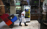An employee wearing a protective face mask and disposable gloves, hauls crates with the aid of a trolley through the popular and normally crowded San Juan food market, in Mexico City, Wednesday, March 25, 2020. Mexico's capital has shut down museums, bars, gyms, churches, theaters, and other non-essential businesses that gather large numbers of people, in an attempt to slow the spread of the new coronavirus. (AP Photo/Fernando Llano)