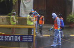 Civic workers sanitize the entrance of Bollywood superstar Amitabh Bachchan's residence after Bachchan and his son tested positive for the coronavirus and were hospitalized in Mumbai, India, Sunday, July 12, 2020. (AP Photo/Rafiq Maqbool)