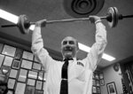 FILE - In this Dec. 5, 1967 file photo, Sen. Strom Thurmond, D-S.C., uses barbells to show his fitness on his 65th birthday in his office in Washington. Some of the more notable recent names in University of South Carolina athletics are asking the school to change the name of its showpiece fitness center, arguing that Thurmond shouldn't be glorified in such a way due to the segregationist views he once held.  The Presidential Commission on University History on Friday, Aug. 21, 2020,  is set to take testimony pushing to rename the Strom Thurmond Wellness and Fitness Center from standouts.  (AP Photo, File)