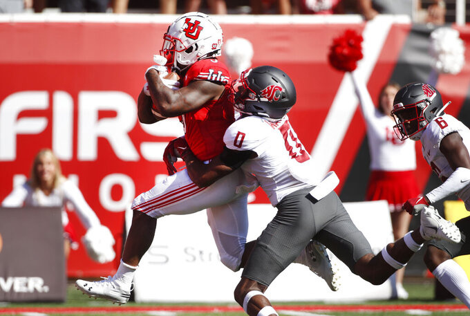Utah running back TJ Pledger (5) runs for a touchdown as Washington State defensive back Jaylen Watson (0) tries to tackle him in the second half, of an NCAA college football game Saturday, Sept. 25, 2021, in Salt Lake City. (AP Photo/George Frey)