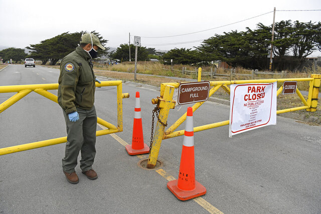 Friends of Santa Cruz State Parks volunteer Alejandro Ortiz closes the gate after allowing an overnight camper access to the parking lot at Francis Beach at Half Moon Bay State Park in Half Moon Bay, Calif., Friday, July 3, 2020. California Gov. Gavin Newsom ordered the parking lots of state beaches to close for the Fourth of July weekend to help prevent the spread of the coronavirus. Half Moon Bay added to the closure by restricting visitors access to the beach. (Jose Carlos Fajardo/Bay Area News Group via AP)