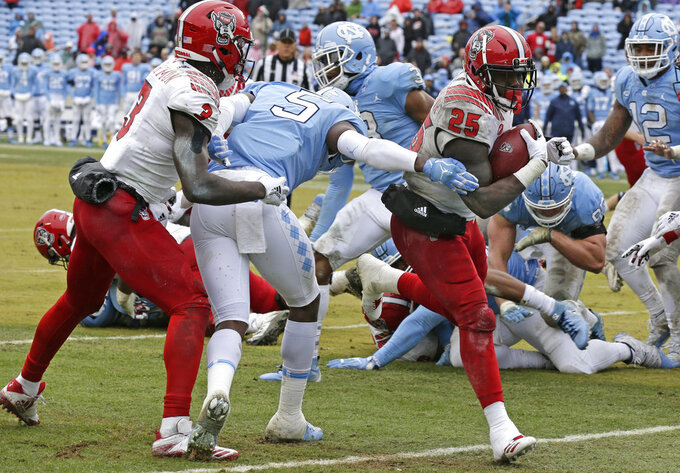 North Carolina State's Reggie Gallaspy II (25) scores a touchdown as Kelvin Harmon (3) blocks North Carolina's Patrice Rene (5) during the second half of an NCAA college football game in Chapel Hill, N.C., Saturday, Nov. 24, 2018. North Carolina State won 43-28 in overtime. (AP Photo/Gerry Broome)