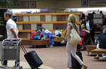 Passengers move through the terminal at the Louis Armstrong Airport in Kenner, La. Friday, July 12, 2019. The system in the Gulf of Mexico is expected to make landfall, possibly as a hurricane, near Morgan City on Saturday morning. (Max Becherer/The Advocate via AP)