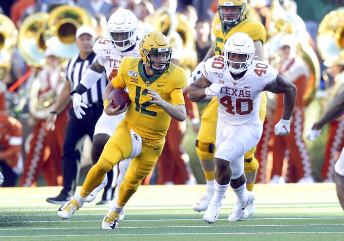 Baylor quarterback Charlie Brewer (12) runs the ball as he is pursued by Texas linebacker Ayodele Adeoye (40) In an NCAA football game Saturday, Nov. 23, 2019, in Waco, Texas. (AP Photo/Richard W. Rodriguez)