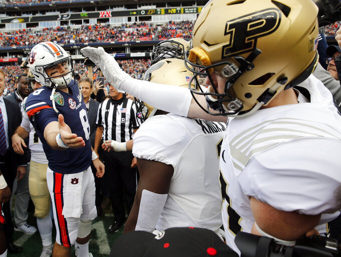 Auburn quarterback Jarrett Stidham, left, greets Purdue safety Jacob Thieneman, right, before the coin toss at the Music City Bowl NCAA college football game Friday, Dec. 28, 2018, in Nashville, Tenn. (AP Photo/Mark Humphrey)