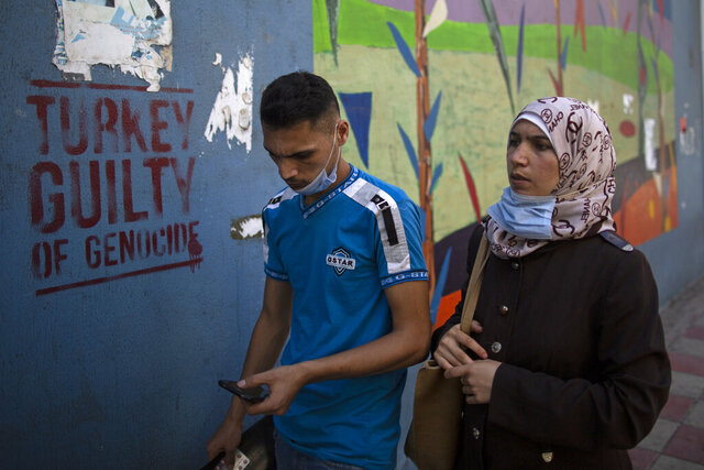 People walk past anti-Turkish graffiti on a wall in the main Armenian district of the northern Beirut suburb of Bourj Hammoud, Lebanon, Tuesday, Oct. 6, 2020. In Bourj Hammoud anger and anxiety are clear among the population over the fighting between Armenian and Azerbaijani forces in the separatist region of Nagorno-Karabakh that broke out on Sept. 27 and has left dozens killed since then. Hundreds of fighters from around the Middle East are heading to Nagorno-Karabakh in Azerbaijan to join rival countries fighting over the region. (AP Photo/Hassan Ammar)