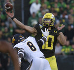 Oregon quarterback Justin Herbert, right, passes under pressure from California's Kuony Deng during the second quarter of an NCAA college football game Saturday, Oct.. 5, 2019, in Eugene, Ore. (AP Photo/Chris Pietsch)