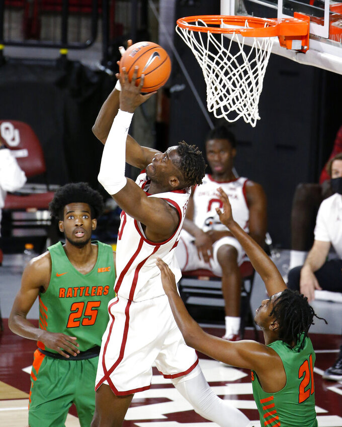 Oklahoma's Rick Issanza (20) goes up against Florida A&M's Johnny Brown (21) and DJ Jones (25) during the second half of an NCAA college basketball game in Norman, Okla., Saturday, Dec. 12, 2020. (AP Photo/Garett Fisbeck)