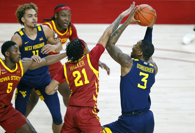 West Virginia forward Gabe Osabuohien, right, drives to the basket as Iowa State guard Jaden Walker, left, defends during the first half of an NCAA college basketball game, Tuesday, Feb. 2, 2021, in Ames, Iowa. (AP Photo/Matthew Putney)