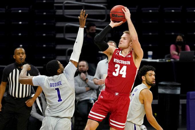 Wisconsin guard Brad Davison, front right, shoots as Northwestern guard Chase Audige guards during the first half of an NCAA college basketball game in Evanston, Ill., Saturday, Feb. 21, 2021. (AP Photo/Nam Y. Huh)