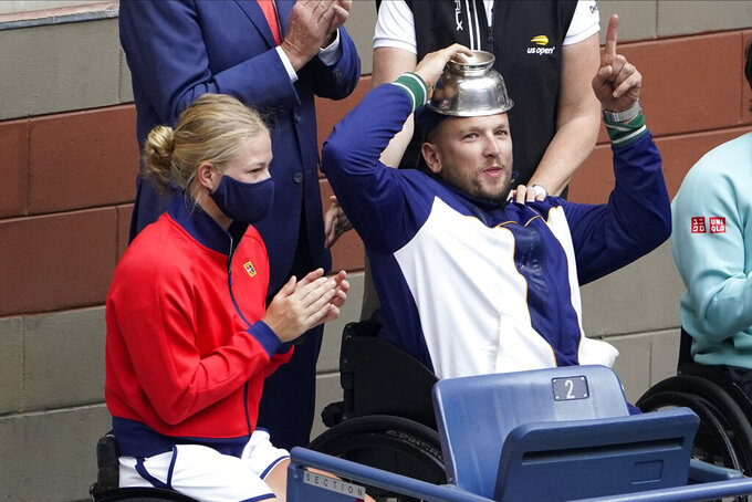 Diede De Groot, of the Netherlands, left, and Dylan Alcott, of Australia react to the crowd while watching play between Novak Djokovic, of Serbia, and Daniil Medvedev, of Russia, during the men's singles final of the US Open tennis championships, Sunday, Sept. 12, 2021, in New York. (AP Photo/Seth Wenig)