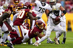 New Orleans Saints running back Alvin Kamara, right, rushes the ball in the second half of an NFL football game against the Washington Football Team, Sunday, Oct. 10, 2021, in Landover, Md. (AP Photo/Al Drago)
