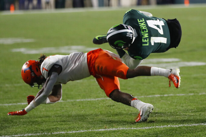 Michigan State quarterback Brian Lewerke (14) flips over Illinois defensive back Stanley Green (7) during the second half of an NCAA college football game, Saturday, Nov. 9, 2019, in East Lansing, Mich. (AP Photo/Carlos Osorio)