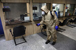 A man wearing protective gear disinfects Health Ministry headquarters because of the new coronavirus, in Tehran, Iran, Saturday, March 7, 2020. (AP Photo/Vahid Salemi)