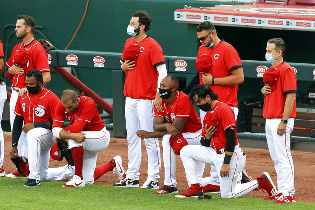 Cincinnati Reds' Phillip Ervin, left, Joey Votto, left middle, Amir Garrett, middle, and Alex Blandino, right, kneel during the national anthem prior to an exhibition baseball game against the Detroit Tigers at Great American Ballpark in Cincinnati, Tuesday, July 21, 2020. (AP Photo/Aaron Doster)