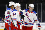 New York Rangers' K'Andre Miller (79) is congratulated by teammates Jacob Trouba (8) and Kaapo Kakko (24), of Finland, after scoring against the New York Islanders during the third period of an NHL hockey game Friday, April 9, 2021, in Uniondale, N.Y. (AP Photo/Jason DeCrow)