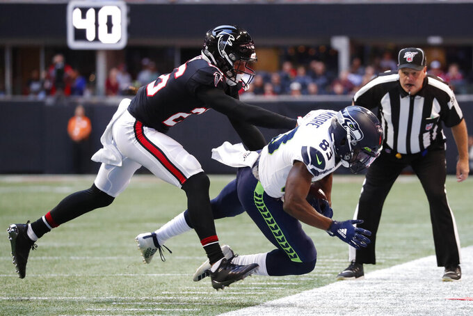 Atlanta Falcons cornerback Isaiah Oliver (26) pushes Seattle Seahawks wide receiver David Moore (83) out of bounds on a reception attempt during the first half of an NFL football game, Sunday, Oct. 27, 2019, in Atlanta. (AP Photo/John Bazemore)