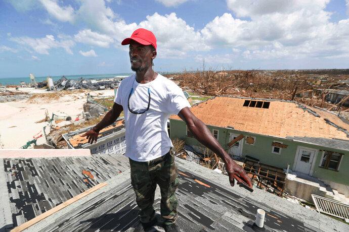Jackson Blatch starts repairs on the roof of his home in Marsh Harbor, Abaco Island, Bahamas, Saturday, Sept. 7, 2019 after Hurricane Dorian hit. (AP Photo/Fernando Llano)