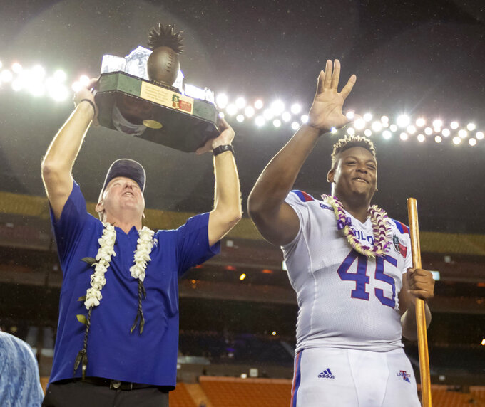 Louisiana Tech head coach Skip Holtz holds up the Hawaii Bowl championship trophy as Louisiana Tech defensive end Jaylon Ferguson (45) waves to the crowd after a Hawaii Bowl NCAA college football game against Hawaii, Saturday, Dec. 22, 2018, in Honolulu. Louisiana Tech beat Hawaii 31-14. (AP Photo/Eugene Tanner)